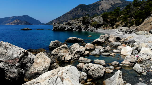 woman floating on rocky beach. - oludeniz stock videos and b-roll footage