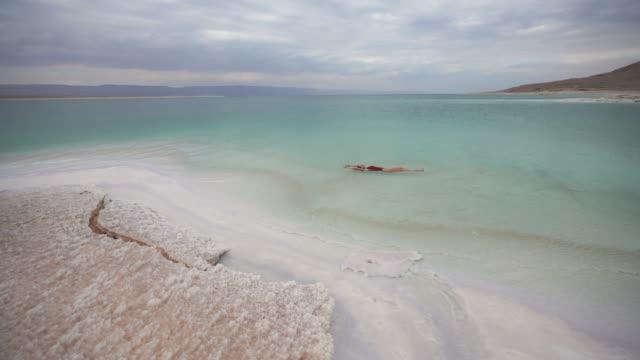 woman floating on water  in dead sea - galleggiare sull'acqua video stock e b–roll