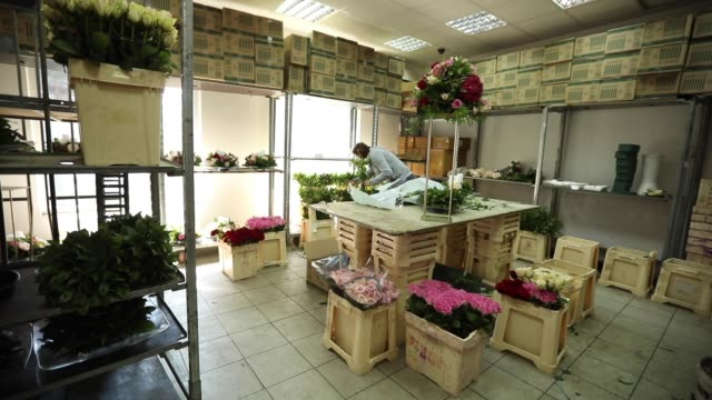 Woman florist working in flower workshop alone