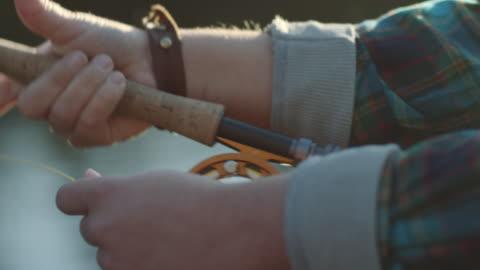 vídeos de stock, filmes e b-roll de woman fly-fishing on river - pescaria