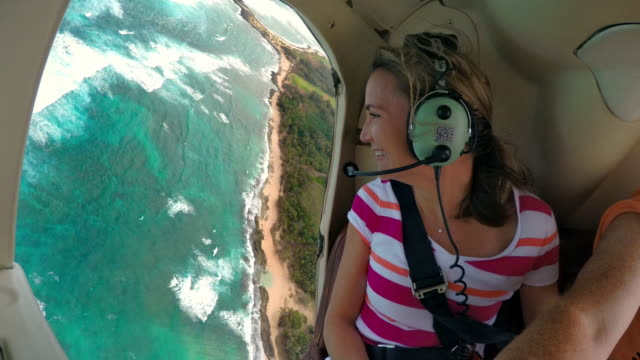 a woman flying in a helicopter with no doors looks out the side smiling - tropical climate stock videos & royalty-free footage