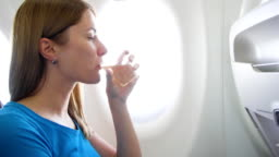 Woman flying in airplane in daytime. Thirsty female drinking wine near window during turbulence