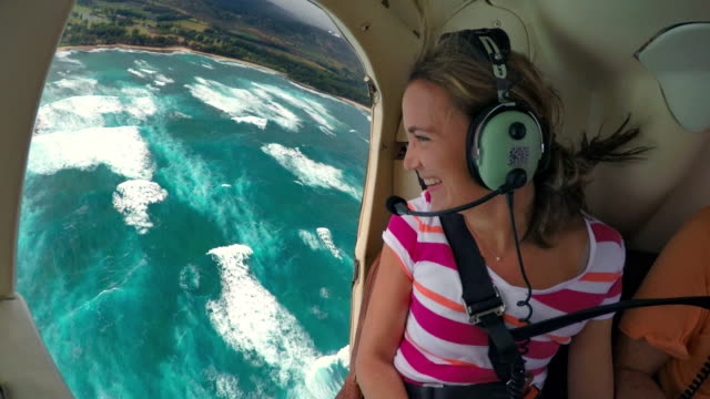 woman flying in helicopter with no doors looks out the side smiling - clima tropicale video stock e b–roll