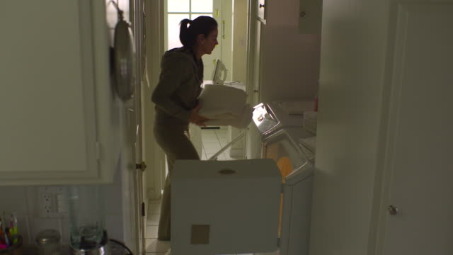 vídeos de stock, filmes e b-roll de ws, pan, woman folding dried linen in laundry room, hollywood, california, usa - dobrando
