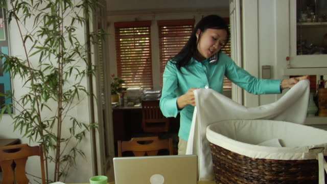 ms woman folding laundry in front of laptop while talking on cordless phone / los angeles, california, usa - cordless phone stock videos & royalty-free footage