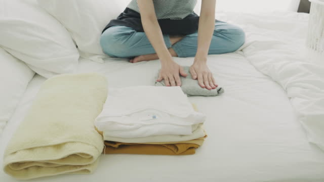 woman folding laundry on the bed