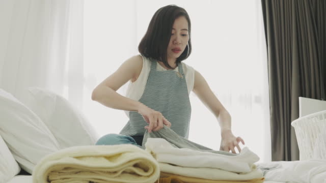 woman folding laundry on the bed - folded stock videos and b-roll footage