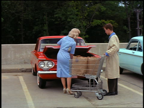 vidéos et rushes de 1960 pan woman followed by bag boy pushing cart to red chevy corvair in grocery store parking lot - 1960