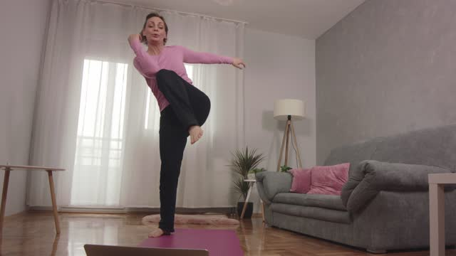 woman following a video tutorial on laptop and working out - one mature woman only stock videos & royalty-free footage
