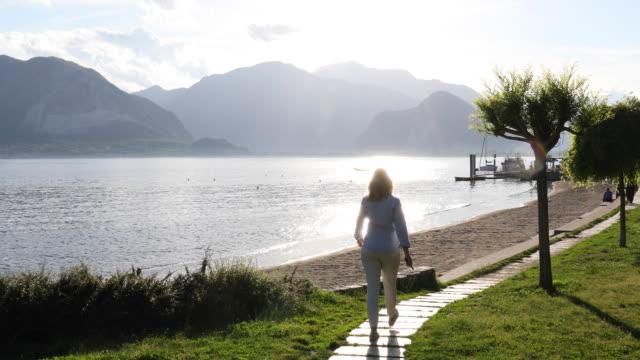 Woman follows lake walkway, mountains distant, sunrise
