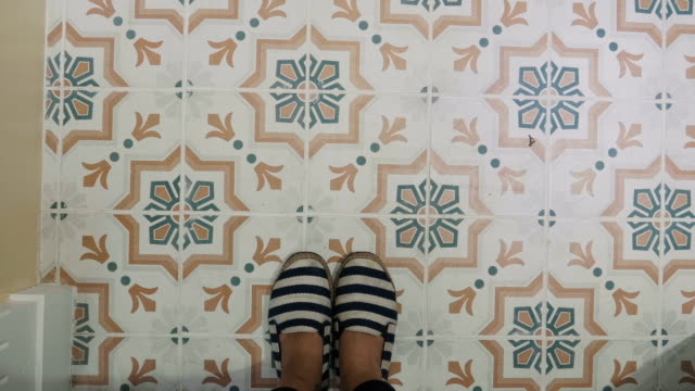 POV of woman foot while walking across retro tile pattern