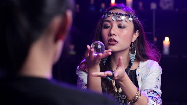 女性の占い師は、別の女性が前に座って、占いを作るためにクリスタルボールを保持しています。 - 魔術師点の映像素材/bロール