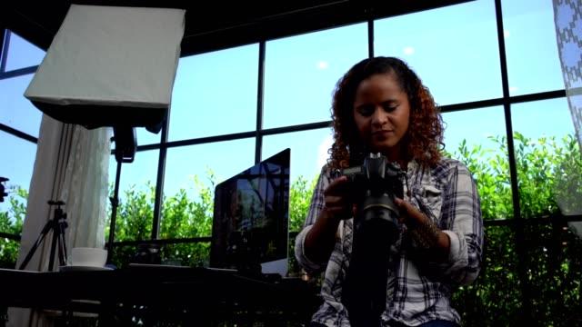 女性フリーランスの写真家がスタジオオフィスで働いています。 - 人の背中点の映像素材/bロール