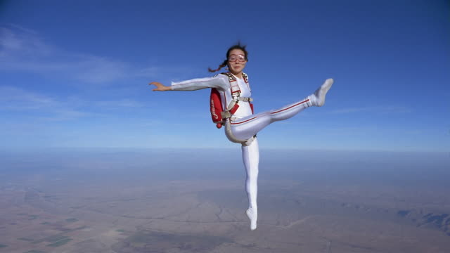 WS Woman freestyle skydiving and performing aerial ballet in mid air above patchwork landscape / Eloy, Arizona, USA