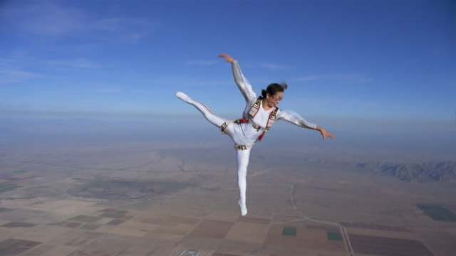 ws woman freestyle skydiving and performing aerial ballet in mid air above patchwork landscape / eloy, arizona, usa - patchwork landscape stock videos and b-roll footage
