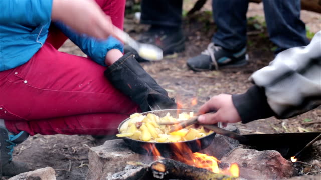 Woman fries a potato on a fire.