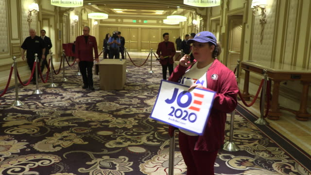 woman from joe biden's campaign stands outside the ballroom as 2020 nevada caucus goers gathered at the grand ballroom at the bellagio to cast their... - democratic party usa stock videos & royalty-free footage