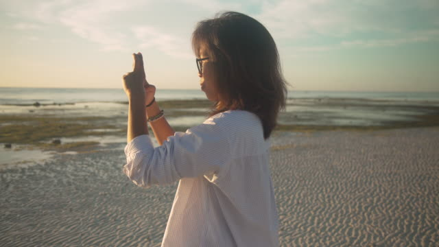 Woman from Philippines taking picture with the smartphone of the sunrise / sunset at Bohol island