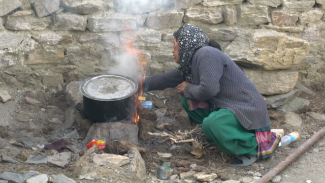 A woman from the village of Karzok in Ladakh, India boiling milk in boiling pot on open fire