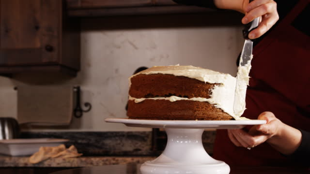 vídeos de stock, filmes e b-roll de woman frosting a cake - equipamento doméstico