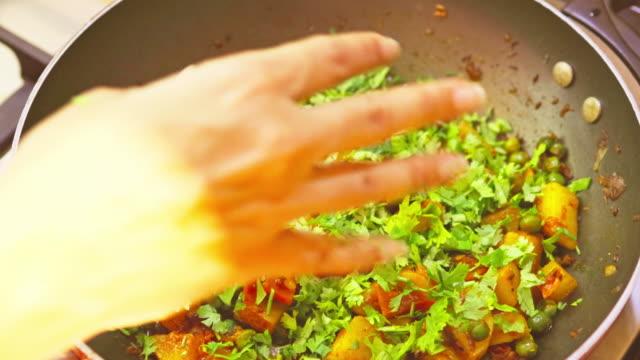 エンドウ豆とドライポテトカレーの上に新鮮なシラントロを飾る女性 - カレー料理点の映像素材/bロール