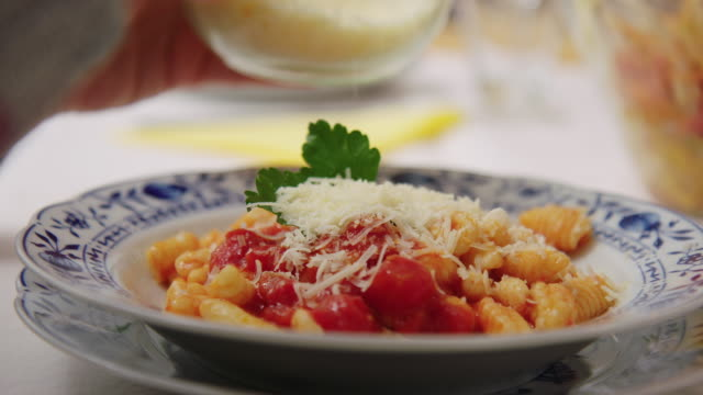 woman garnishing pasta with grated cheese - grated stock videos & royalty-free footage