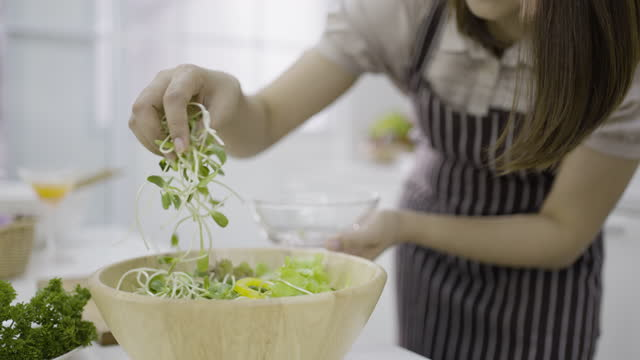woman garnishing salad with sprouted micro greens - environmental conservation stock videos & royalty-free footage