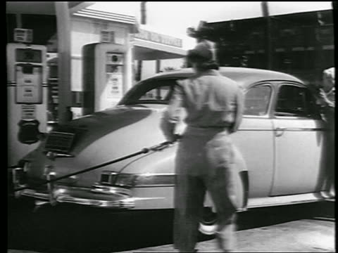 b/w 1944 pan woman gas station attendant pulling air hose to tire as woman in background washes windshield - gas station attendant stock videos and b-roll footage