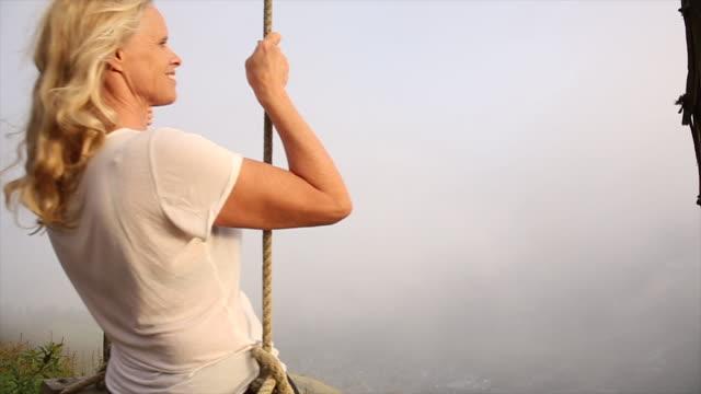 Woman gently swings above valley below, in mist