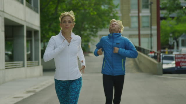 Woman gesturing to man to catch up while running in city / Salt Lake City, Utah, United States