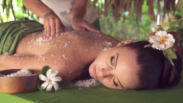 a woman gets a massage at a spa in a hotel resort. - spa stock videos & royalty-free footage