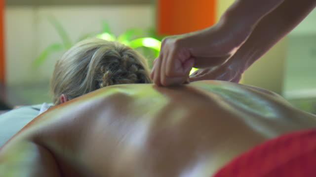 a woman gets a massage at a spa. - kurbehandlung stock-videos und b-roll-filmmaterial