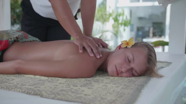 vidéos et rushes de a woman gets a massage by a masseuse at a resort hotel spa. - spa