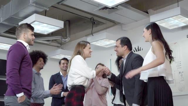 frau bekommt eine promotion und ihre mitarbeiter gratulieren ihr im büro - lateinische schrift stock-videos und b-roll-filmmaterial
