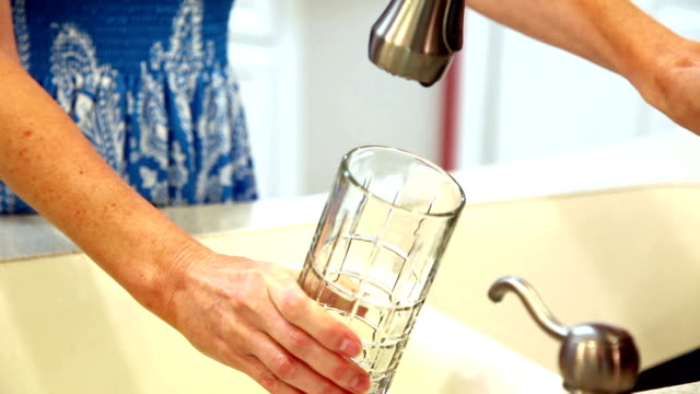 Woman gets drink of clean water in glass. Kitchen sink.