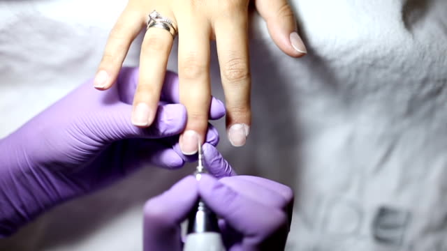 Woman gets her nails cleaned