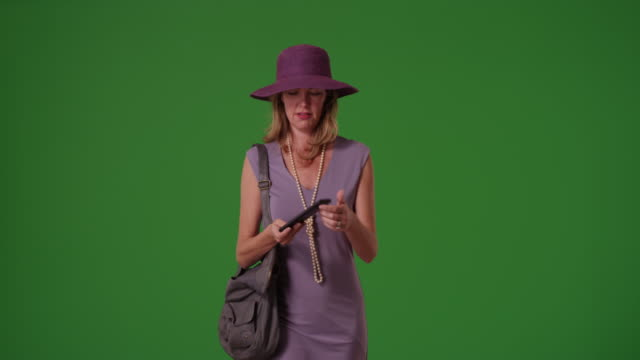 vidéos et rushes de woman gets her smart phone out to look for directions on green screen - regarder autour de soi
