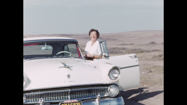 A woman gets into her vintage car on a beach.