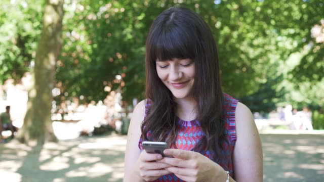 vidéos et rushes de woman gets phone from pocket and answer message - track in - répondre