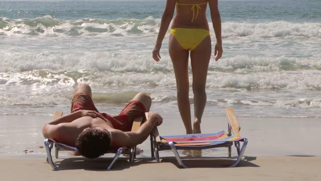 vídeos y material grabado en eventos de stock de woman gets up from beach chair and walks into the water at the beach while man continues lounging - bañador de natación