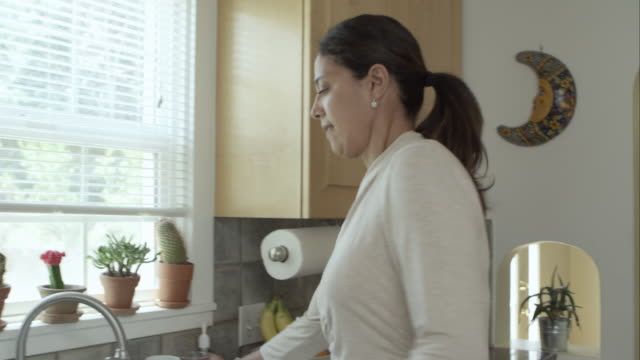 Woman getting a glass of water in the kitchen.