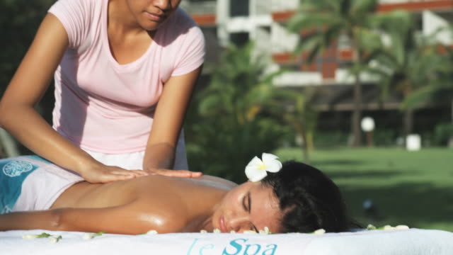 stockvideo's en b-roll-footage met woman getting a massage on the beach - french overseas territory