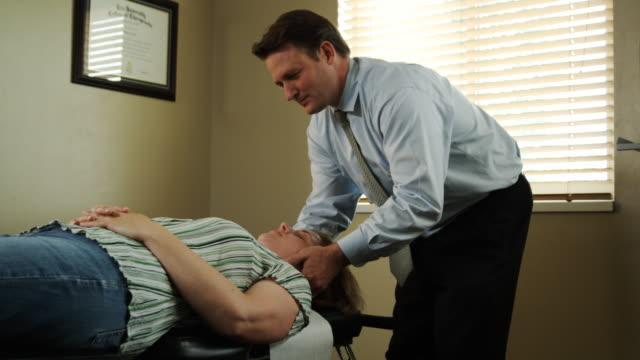 woman getting adjusted at the chiropractor - menschlicher hals stock-videos und b-roll-filmmaterial