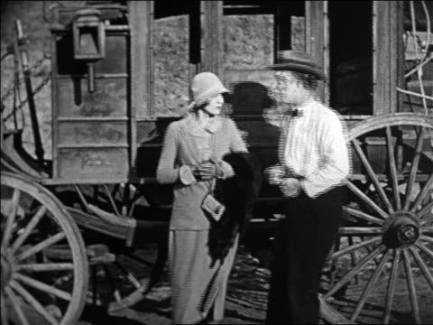 stockvideo's en b-roll-footage met b/w 1924 woman getting angry at nerdy man after stagecoach holdup / feature - 1924