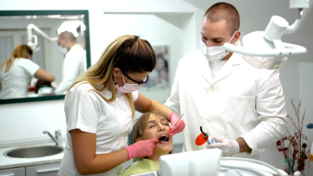 woman getting dental treatment - protective mask workwear stock videos and b-roll footage
