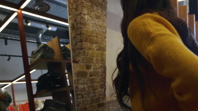 vídeos de stock e filmes b-roll de woman getting dressed - cabine de loja