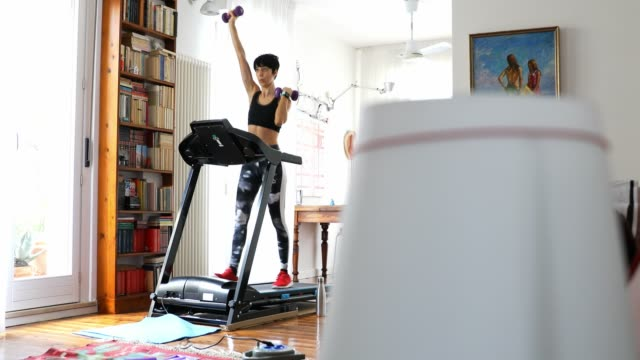 woman getting fit and doing home training in the living room - leggings stock videos & royalty-free footage