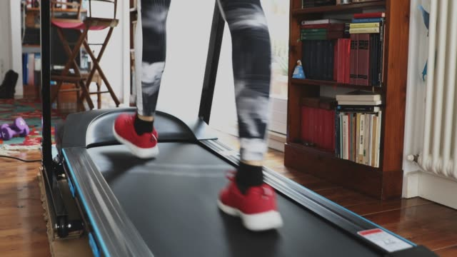woman getting fit and doing home training in the living room - treadmill stock videos & royalty-free footage