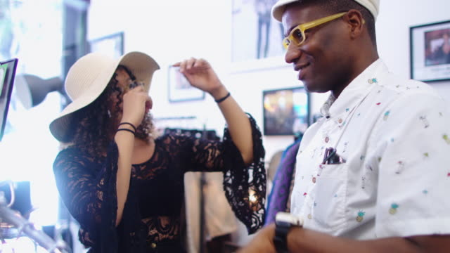 vídeos de stock e filmes b-roll de woman getting friend to try on hat in vintage store - 30 seconds or greater