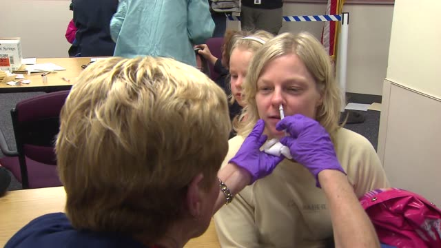 stockvideo's en b-roll-footage met woman getting h1n1 swine flu nasal spray on october 24, 2013 in chicago, illinois - varkensgriep